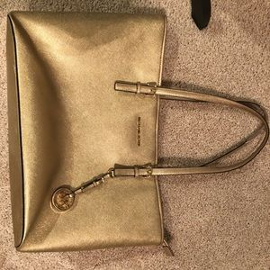 Gold Michael Kors tote with laptop liner inside.